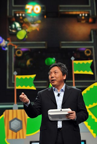 "FILE - In this June 5, 2012 publicity file photo provided by Nintendo of America, Katsuya Eguchi, Producer of Software Development for Nintendo, shows off ""Luigi's Ghost Mansion,"" one of 12 attractions in Nintendo Land, an upcoming game for the new Wii U home console, during the Nintendo All-Access Presentation at E3 2012 in Los Angeles. The Wii U GamePad controller makes asymmetric gameplay possible by allowing for multiple experiences in the same game at the same time. (AP Photo/Nintendo of America, Vince Bucci, File)"