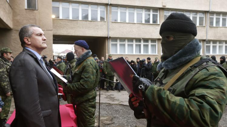 Aksyonov, Crimea's pro-Russian prime minister, stands as a member of a pro-Russian self defence unit takes an oath to Crimea government in Simferopol