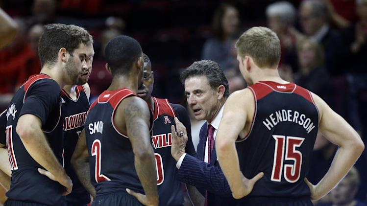 Louisville head coach Rick Pitino, second from right, talks to his