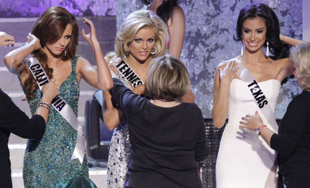 From left, Alyssa Campanella, Miss California, Ashley Elizabeth Durham, Miss Tennessee and Ana Christina Rodriguez, Miss Texas, have their sashes replaced during a break at the 2011 Miss USA pageant, Sunday, June 19, 2011, in Las Vegas. (AP Photo/Julie Jacobson)