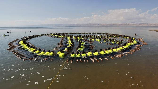 Employees and management members of hotels near Dead Sea form a floating image at the Dead Sea beach
