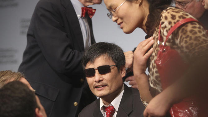 FILE- In this May 31, 2012 file photo, blind Chinese dissident Chen Guangcheng talks with people after speaking at the Council on Foreign Relations in New York. A spokesman for New York University confirms Thursday, June 13, 2013, that Chen will be leaving his position as a special student at the university's Asia Law Institute. (AP Photo/Seth Wenig, File)