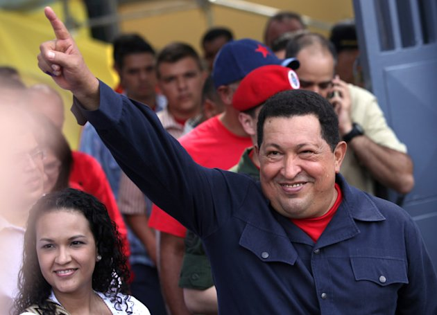 Accompanied by his daughter Rosa Virginia, left, Venezuela's President Hugo Chavez gestures to supporters as he leaves the polling station after voting in the presidential election in Caracas, Venezue