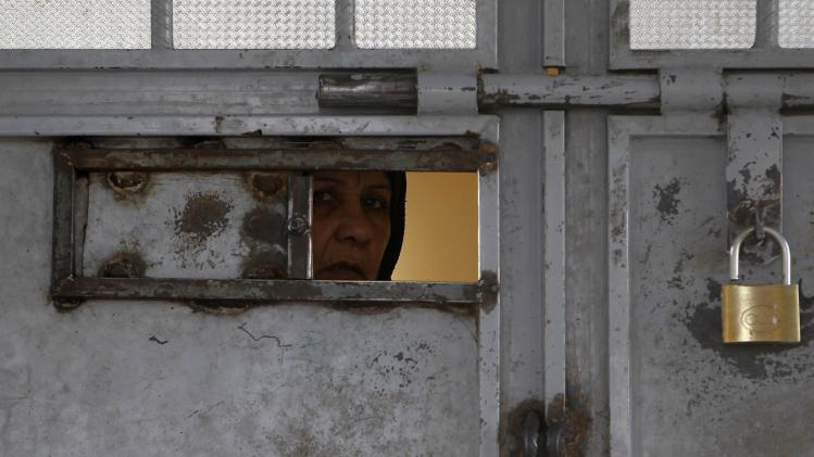 An Afghan woman looks out from a viewing panel in a door at Herat prison