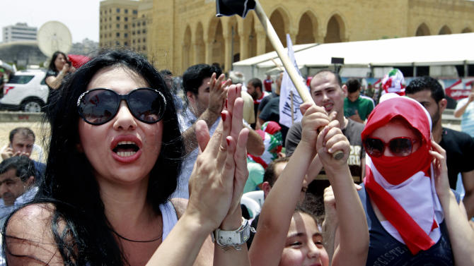 Lebanese and Syrian activists chant pro-Syrian revolution slogans during a protest against the participation of Hezbollah in the Syrian war, at Martyrs square in Beirut, Lebanon, Sunday, June 9, 2013. A senior Lebanese military official says clashes have erupted outside the Iranian embassy in the capital between protesters opposing Hezbollah's participation in the Syrian war and unidentified locals, killing one demonstrator. (AP Photo/Bilal Hussein)