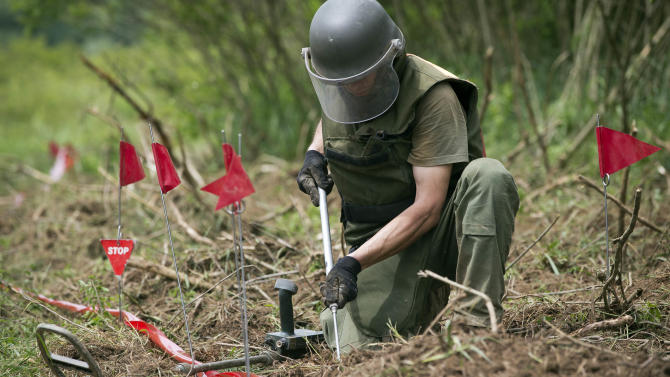 Ante Ivanda, a de-miner, searches for land mines in Petrinja, central Croatia, Friday, May 17, 2013.  Croatian researches, working on a unique method to find unexploded mines that are littering their country and the rest of the Balkans, are confident they can use bees for detecting land mines. (AP Photo/Darko Bandic)