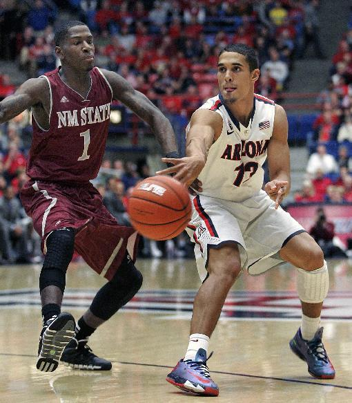 Arizona's Nick Johnson (13) passes the ball in front of New Mexico States' DK Eldridge (1) in the first half of an NCAA college basketball game on Wednesday, Dec. 11, 2013 in Tucson, Ariz