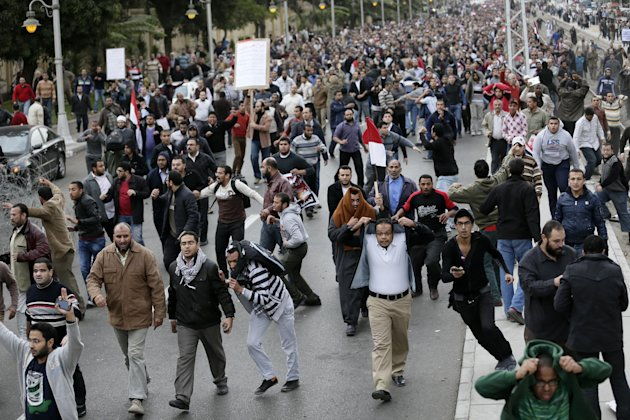 Egyptian President Mohammed Morsis supporters clash with opponents, not pictured, outside the presidential palace, in Cairo, Egypt, Wednesday, Dec. 5, 2012. Wednesdays clashes began when thousands of Islamist supporters of Morsi descended on the area around the palace where some 300 of his opponents were staging a sit-in. (AP Photo/Hassan Ammar)