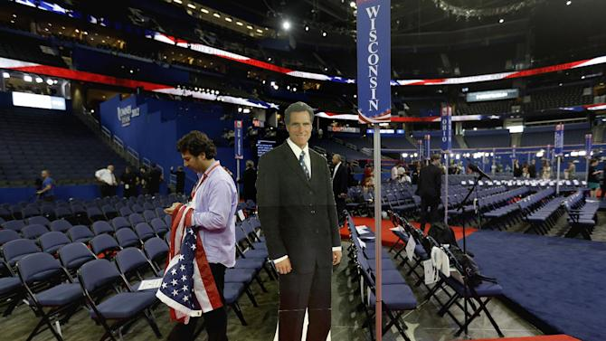 A cardboard cutout of Republican presidential nominee, former Massachusetts Gov. Mitt Romney stands on the floor of the Republican National Convention as a member of a German television crew works at left, Wednesday, Aug. 29, 2012, in Tampa, Fla. (AP Photo/David Goldman)