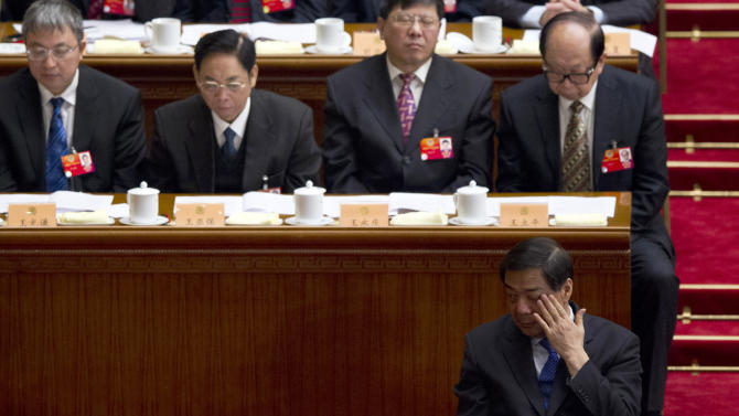 In this March 13, 2012 photo, former Chongqing Communist Party Secretary Bo Xilai, bottom, rubs his face during the closing session of the Chinese People's Political Consultative Conference held in Beijing's Great Hall of the People, China. The new leadership in the southwestern Chinese city beset by a murder scandal that took down its Communist Party boss says lessons must be learned from the embarrassing episode and efforts made to repair the city's image. (AP Photo/Alexander F. Yuan)