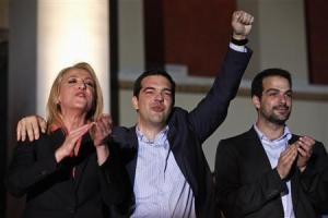 Leader of leftist Syriza party Tsipras raises his arm as he celebrates with newly elected governor of the wider Athens region Dourou and mayoral runner up for the city of Athens Sakellaridis, in Athens