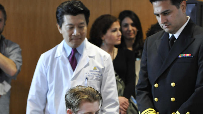Retired Infantryman Brendan M. Marrocco wheels himself into a news conference followed by lead surgeon W.P. Andrew Lee, M.D., Tuesday, Jan. 29. 2013 at Johns Hopkins hospital in Baltimore.  Marrocco received a transplant of two arms from a deceased donor after losing all four limbs in a 2009 roadside bomb attack in Iraq. (AP Photo/Gail Burton)
