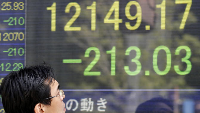 A man looks at the latest Nikkei stock index on display in an electric signboard of a securities firm in Tokyo Thursday, April 4, 2013. Weak economic reports on hiring and service industry growth in the U.S. sent Asian stock markets lower Thursday. (AP Photo/Koji Sasahara)