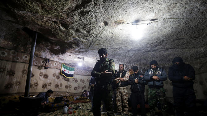 Free Syrian Army fighters pray inside a cave at Jabal al-Zaweya in Idlib, Syria, Sunday Feb. 24, 2013. Syrian rebels used captured tanks to launch a fresh offensive on a government complex housing a police academy near Aleppo and clashed with government troops protecting the strategic installation on Sunday. (AP Photo/Hussein Malla)