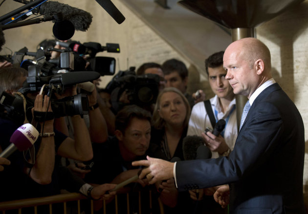 British Foreign Minister William Hague, right, talks to media representatives upon his arrival for a meeting of the Action Group for Syria at the European headquarters of the United Nations,  in Genev