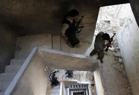 Free Syrian Army fighters carry their weapons as they walk down a building in the old city of Aleppo