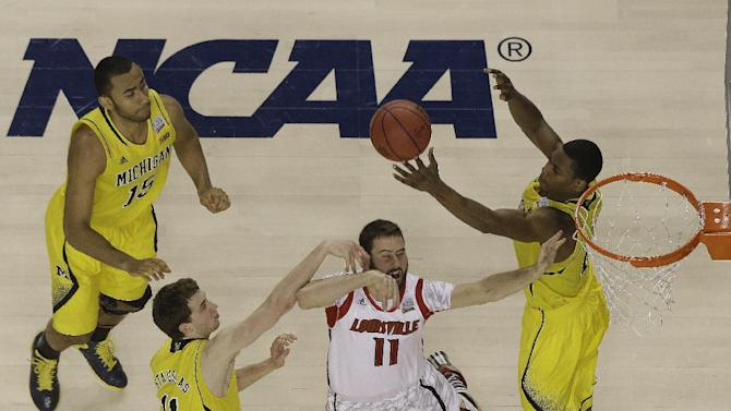 Louisville guard/forward Luke Hancock (11) loses the ball as Michigan forward Glenn Robinson III (1) and Michigan guard Nik Stauskas (11) defend during the first half of the NCAA Final Four tournament college basketball championship game Monday, April 8, 2013, in Atlanta. (AP Photo/David J. Phillip)