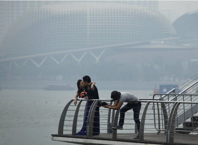 Couple has their wedding photos taken in front of the hazy skyline of Singapore