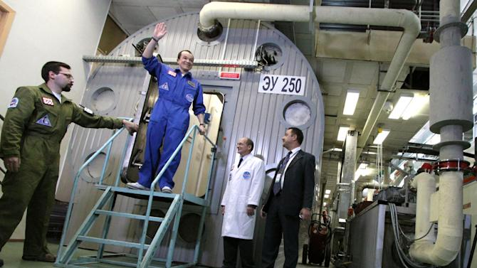FILE This Nov. 4, 2011 file photo released by Moscow's  Institute for Medical and Biological Problems Russia, shows researcher Sukhrob Kamolov leaving a set of windowless modules after a grueling 520-day simulation of a flight to Mars. Astronauts have a down-to-Earth problem that could be even worse on a long trip to Mars: They can't get enough sleep. And over time, the lack of slumber can turn intrepid space travelers into drowsy couch potatoes, a new study shows. In a novel experiment, six volunteers were confined in a cramped mock spaceship in Moscow to simulate a 17-month voyage.  It made most of the would-be spacemen act like birds and bears heading into winter, gearing for hibernation. (AP Photo/IMBP, Oleg Voloshin, Pool, File)