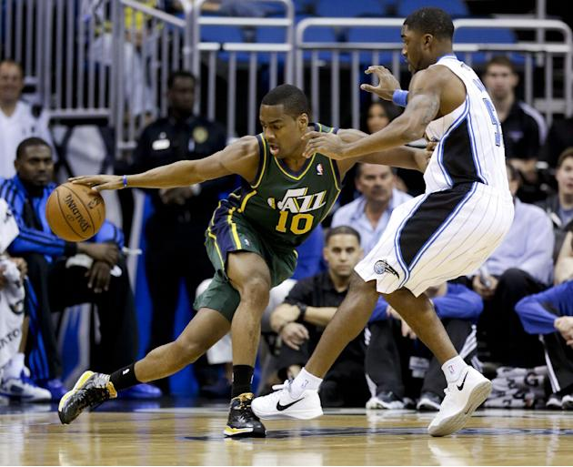 Utah Jazz's Alec Burks (10) makes a move to get around Orlando Magic's E'Twaun Moore, right, during the first half of an NBA basketball game in Orlando, Fla., Wednesday, Dec. 18, 2013