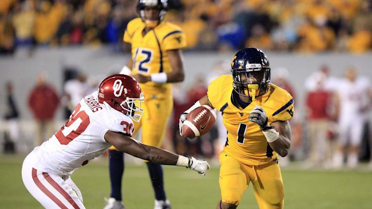 West Virginia wide receiver Tavon Austin (1) slips past Oklahoma's Javon Harris (30) for a rushing touchdown during the third quarter of their NCAA college football game against Oklahoma in Morgantown, W.Va., on Saturday, Nov. 17, 2012. Oklahoma won 50-49. (AP Photo/Christopher Jackson)