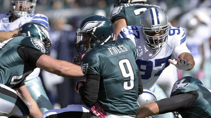 FILE - In this Oct. 20, 2013, file photo, Philadelphia Eagles quarterback Nick Foles (9) is sacked by Dallas Cowboys defensive end George Selvie (99) as defensive tackle Jason Hatcher (97) helps on the play during an NFL football game in Philadelphia. Foles is constantly reminded about the first time the Eagles played the Cowboys this season. Both teams were 3-3 when Dallas came to Philadelphia, shut down coach Chip Kelly's high-flying offense and knocked Foles out of the game with a concussion at the end of the third quarter. (AP Photo/Michael Perez, File)