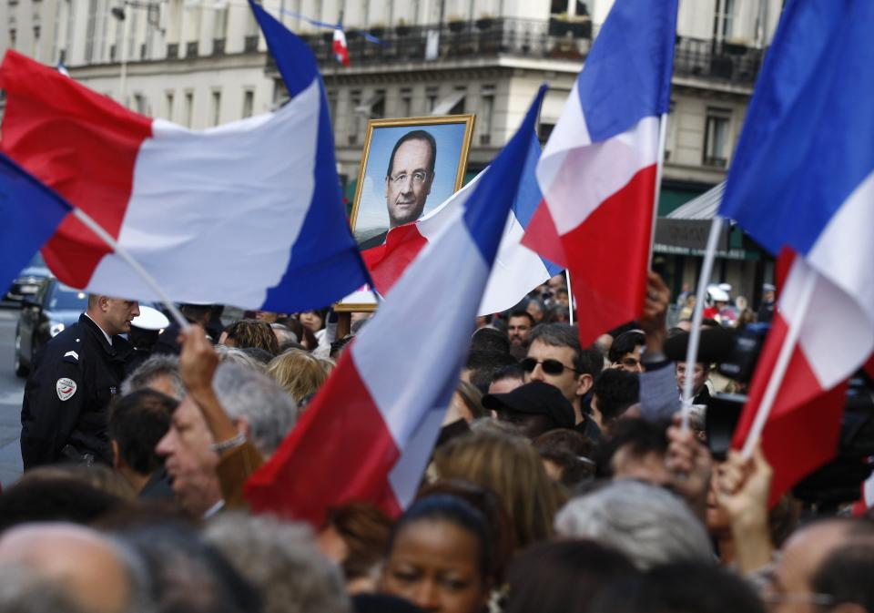 Supporters of outgoing French President Nicolas Sarkozy and new President Francois Hollande, seen on poster, gather outside the Elysee Palace, Tuesday, May 15, 2012 in Paris during the handover ceremony. (AP Photo/Michel Euler)