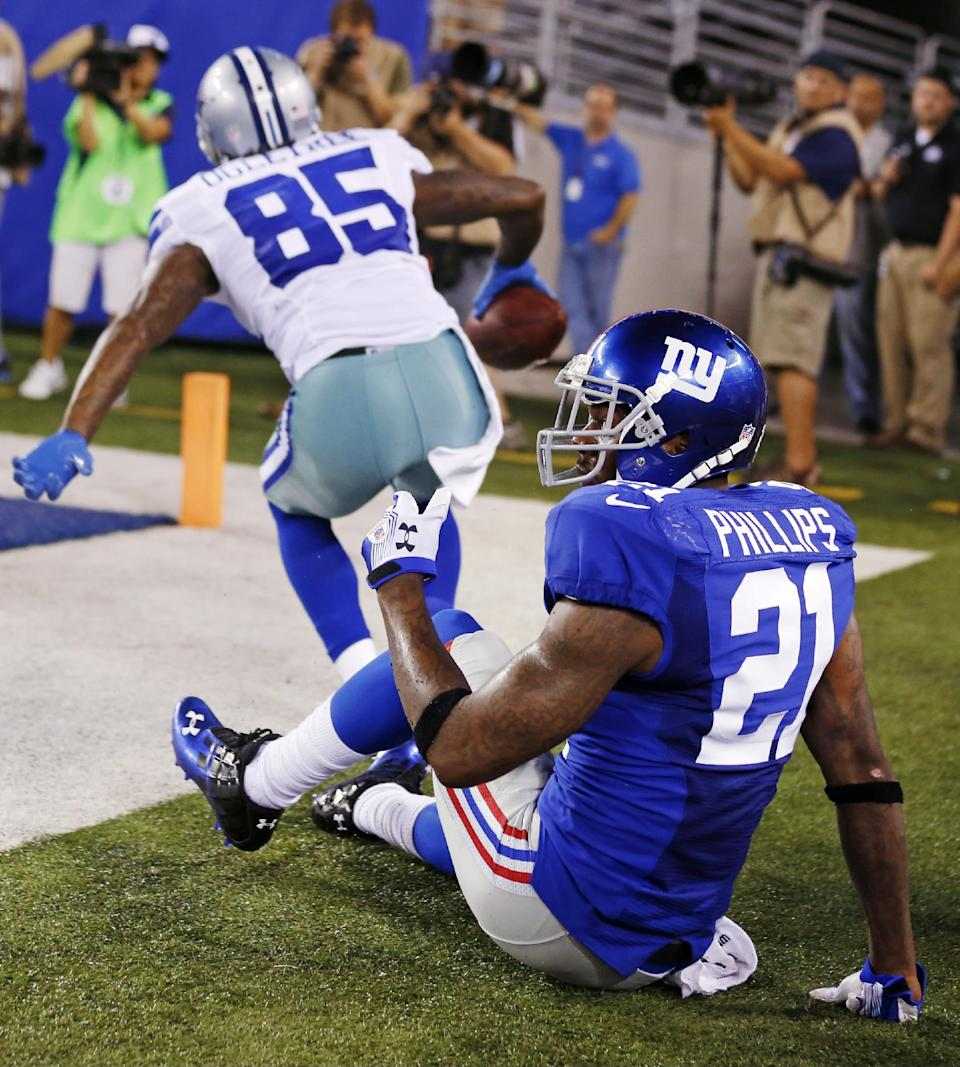 New York Giants strong safety Kenny Phillips (21) reacts as Dallas Cowboys wide receiver Kevin Ogletree (85) celebrates catching a touchdown pass during the second half of an NFL football game, Wednesday, Sept. 5, 2012, in East Rutherford, N.J. (AP Photo/Julio Cortez)