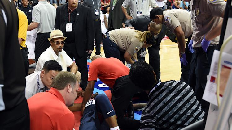 Paul George of the 2014 USA Basketball Men's National Team is tended to as he lies on the court after badly injuring his leg defending a play during a USA Basketball showcase match at the Thomas & Mack Center on August 1, 2014 in Las Vegas, Nevada