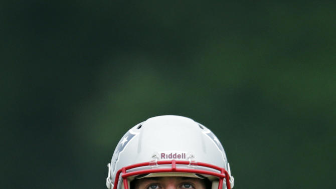New England Patriots quarterback Tim Tebow looks upward as he prepares to throw during a NFL football practice in Foxborough, Mass., Tuesday June 11, 2013. (AP Photo/Charles Krupa)