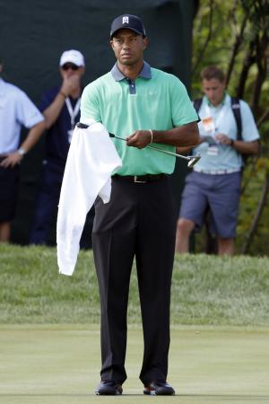Tiger Woods wipes off his club during the first round of the BMW Championship golf tournament at Conway Farms Golf Club in Lake Forest. Ill., Thursday, Sept. 12, 2013. (AP Photo/Charles Rex Arbogast)