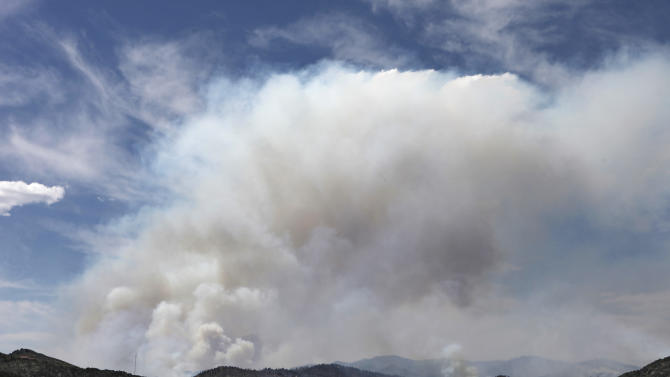 A plume of smoke rises above the Waldo Canyon fire west of Manitou Springs, Colo., on Monday, June 25, 2012. The fire, one of at least a half-dozen wildfires in Colorado on Monday, has blackened 5.3 square miles and displaced about 6,000 people since it started Saturday, June 23, but no homes have been destroyed. (AP Photo/Ed Andrieski)