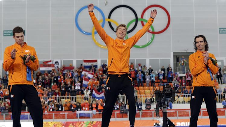 Athletes for the Netherlands: Gold medalist Jorrit Bergsma, center, raises his arms in celebration, applauded by silver medalist Sven Kramer, left, and bronze medalist Bob de Jong, after the men's 10,000-meter speedskating race at the Adler Arena Skating Center during the 2014 Winter Olympics in Sochi, Russia, Tuesday, Feb. 18, 2014. (AP Photo/Patrick Semansky)