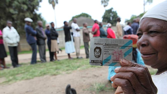 An elderly woman shows her identity card while waiting to cast her vote during a referendum in Harare, Zimbabwe, Saturday, March, 16, 2013. The country is holding the referendum on a new  constitution which  will pave way for the adoption of the draft constitution as the country prepares to hold elections  later in the year. (AP Photo/Tsvangirayi Mukwazhi)
