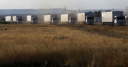 Trucks of a Russian convoy carrying humanitarian aid for Ukraine drive before parking at a camp near Donetsk located in Rostov Region
