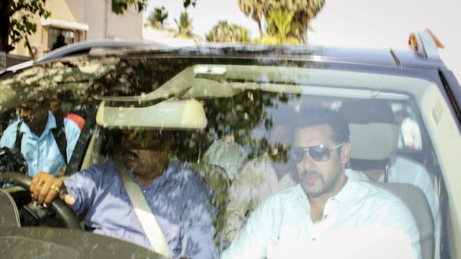 Bollywood actor Salman Khan sits in a car as he leaves his house for court in Mumbai