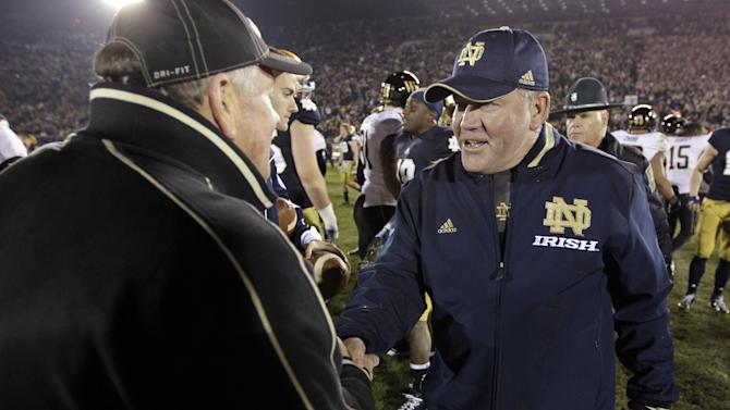 Notre Dame head coach Brian Kelly, right, meets with Wake Forest head coach Jim Grobe following an NCAA college football game in South Bend, Ind., Saturday, Nov. 17, 2012. Notre Dame defeated Wake Forest 38-0. (AP Photo/Michael Conroy)