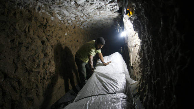 In this Thursday, Oct. 28, 2010 file photo, a Palestinian smuggler moves refrigerators through a tunnel from Egypt to the Gaza Strip under the border in Rafah, southern Gaza Strip. Hamas had hoped the Islamists who took charge in Egypt  this summer -- fellow members of the region's Muslim Brotherhood -- would swiftly turn the shared border crossing into a free-flowing trade route, ending Gaza's five-year isolation from the world and making the tunnels obsolete. (AP Photo/Eyad Baba, File)