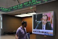 An employee at the Athens stock exchange walks past a television showing Antonis Samaras, the country's newly elected prime minister. Troubled eurozone nations agreed to act quickly to save Spain's banks, and to send international creditors to Greece for an update from the new government