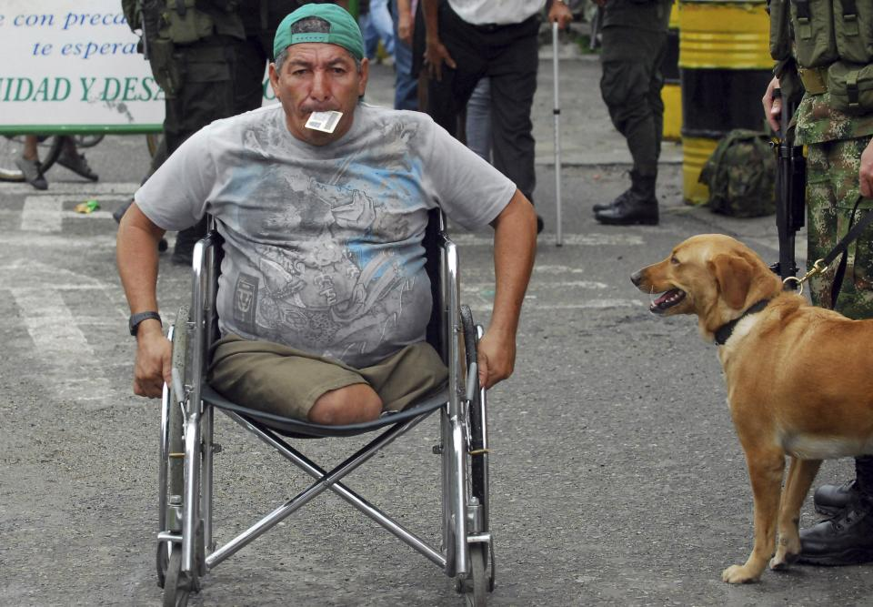 A man steers his wheelchair towards a polling station during local and regional elections in Corinto, southern Colombia, Sunday, Oct. 30, 2011. Colombians went to the polls Sunday to choose mayors, state governors and local assemblies.  (AP Photo/Carlos Julio Martinez)