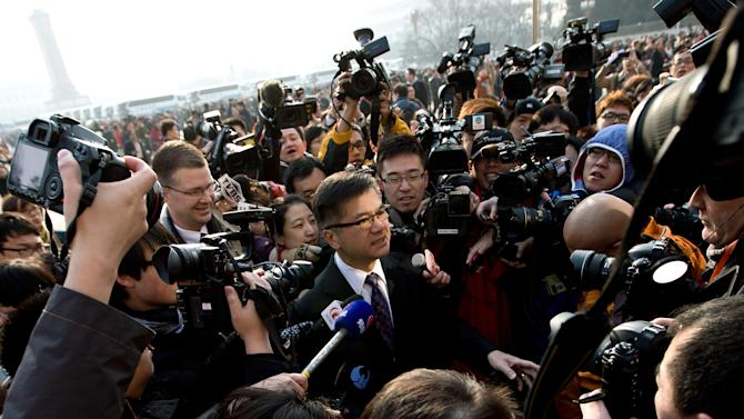 U.S. Ambassador to China Gary Locke, center, is mobbed by journalists as he attends the opening session of the annual National People's Congress at the Great Hall of the People in Beijing Tuesday, March 5, 2013. The United States and China have reached an agreement on a new draft sanctions resolution to punish North Korea for its latest nuclear test, U.N. diplomats said late Monday. (AP Photo/Andy Wong)