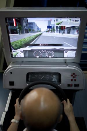 In this May 30, 2011 photo, Dr. Jin Huiqing tries a driving simulator produced by his company in a lab of Anhui Sanlian University in Hefei, in central China's Anhui province. In China, where someone is killed in traffic every five minutes, Jin has an unusual approach for making roads safer: Treat bad driving like a disease you can diagnose before the driver even gets near a car. (AP Photo/Alexander F. Yuan)