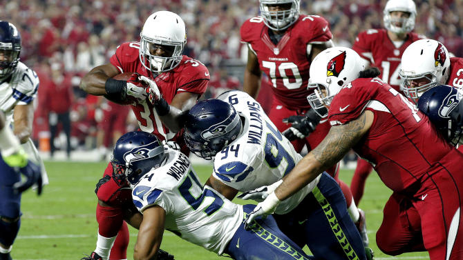 Arizona Cardinals running back Stepfan Taylor (30) is stopped by Seattle Seahawks' Kevin Williams (94) and Bobby Wagner (54) during the first half of an NFL football game, Sunday, Dec. 21, 2014, in Glendale, Ariz. (AP Photo/Ross D. Franklin)