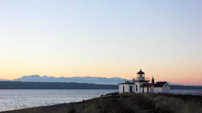In this image taken Jan. 16, 2013, a lighthouse lines the beach at Discovery Park in Seattle. At 534 acres, Discovery Park is the largest park in the city and it features seaside bluffs, views of the Puget Sound, trails, a light house and a beach.  (AP Photo/Manuel Valdes )