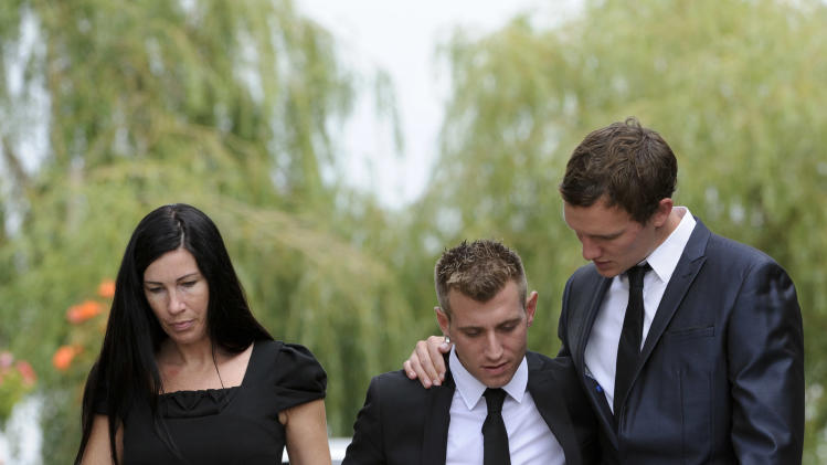 Mourners react as they leave Edgwarebury Cemetery in London, Tuesday July 26, 2011, after attending the funeral of singer Amy Winehouse.  The soul diva, who had battled alcohol and drug addiction, was found dead Saturday at her London home. She was 27. (AP Photo/Jonathan Short)