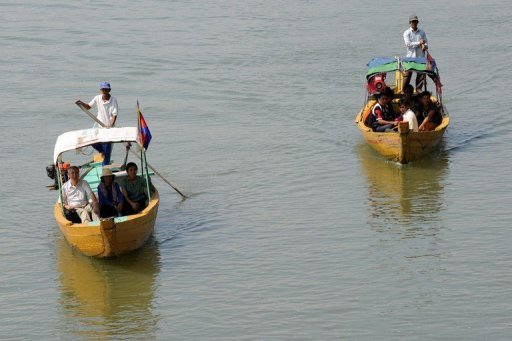 This photo taken on December 6, 2012 shows Cambodians and foreign tourists on boats to spot dolphins along the Mekong river. There is a ban on hunting dolphins in the Mekong, but old habits die hard. Some 77 unarmed guards patrol the Cambodian stretch of the Mekong on the lookout for activities that could harm dolphins