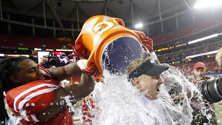 Mississippi coach Hugh Freeze gets dunked by Mississippi offensive linesman Justin Bell after Mississippi defeated Boise State 35-13 in an NCAA college football game Thursday, Aug. 28, 2014, in Atlanta