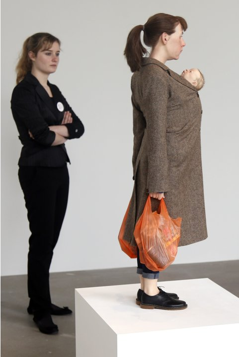 "A visitor looks at a sculpture entitled ""Woman with Shopping, 2013"" by artist Ron Mueck during his exhibition at the Fondation Cartier pour l'art contemporain in Paris"