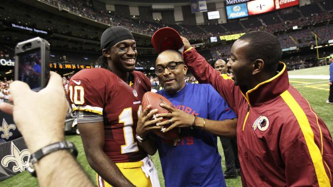 Washington Redskins quarterback Robert Griffin III (10) poses for a photo with filmmaker Spike Lee, center, after an NFL football game against the New Orleans Saints in New Orleans, Sunday, Sept. 9, 2012. The Redskins won 40-32. (AP Photo/Matthew Hinton)