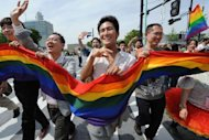 Gay people carry a rainbow flag as they march on the street during the Tokyo Rainbow Pride 2012 in Tokyo. Some 2,500 people marched in the parade in Tokyo on Sunday, vowing to transform a low-profile campaign for the rights of sexual minorities into a major movement in Japan